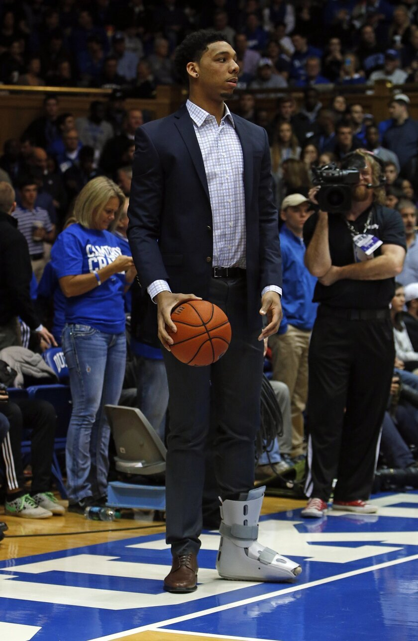 Duke's Jahlil Okafor wears a protective boot on his foot before an NCAA college basketball game against Clemson in Durham, N.C., Saturday, Feb. 21, 2015. Okafor suffered an injury while playing against North Carolina earlier in the week. (AP Photo/Karl B DeBlaker)