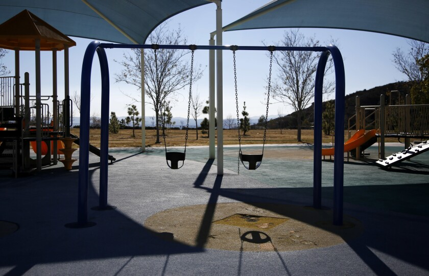 A playground sits empty at a park in Porter Ranch.