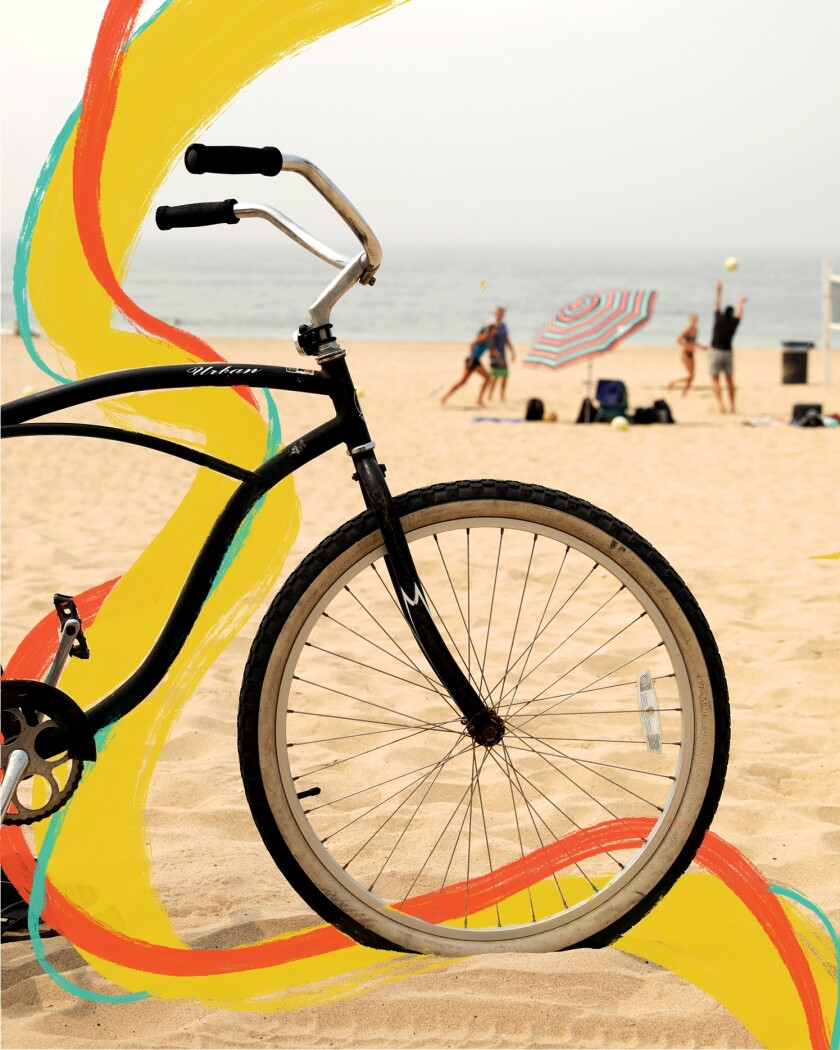 A bicycle on the beach with people playing beach volleyball in the background.