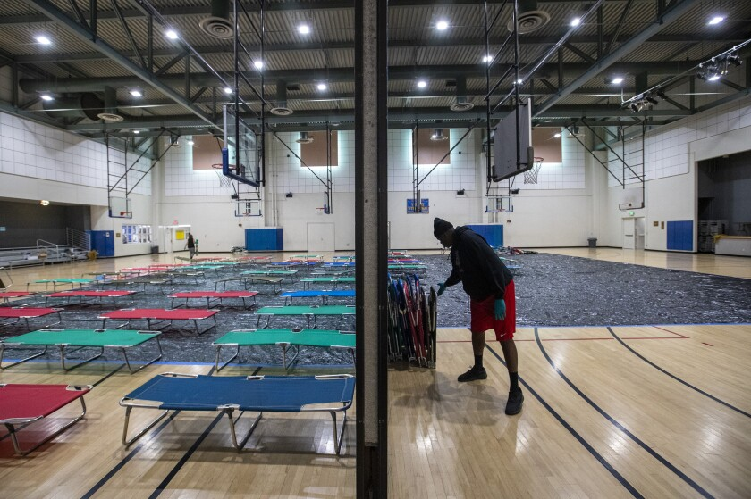 L.A. parks and recreation staffer Chris Smith helps set up cots at Westwood Recreation Center in March