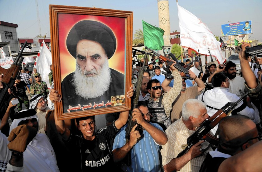 Iraqi Shiite tribal fighters chant and hold a poster of Grand Ayatollah Ali Sistani. On Friday, Sistani called on Iraqi leaders to form a new government with broad national acceptance.