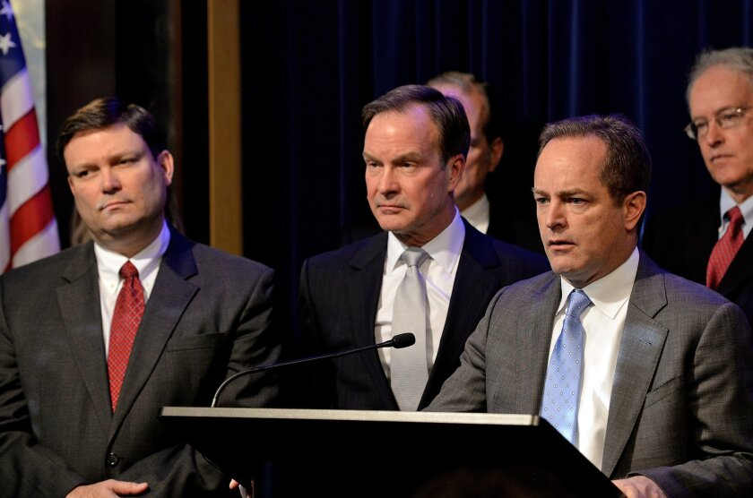Michigan Attorney General Bill Schuette, center, announces Todd Flood, right, a former assistant prosecutor for Wayne County, and retired Detroit FBI chief Andrew Arena, left, will spearhead an investigation and serve as special counsel in the investigation into Flint's lead-tainted water during a news conference Monday, Jan. 25, 2106 in Lansing, Mich. (Dave Wasinger/Lansing State Journal via AP) MANDATORY CREDIT