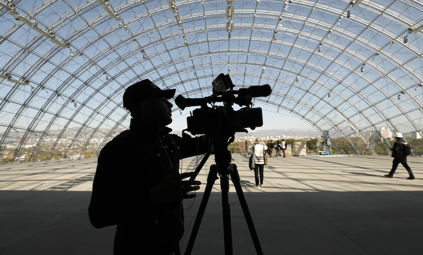 Members of the media check out the glass-domed terrace atop architect Renzo Piano's concrete sphere during a Friday walk-through at the Academy Museum of Motion Pictures in L.A.