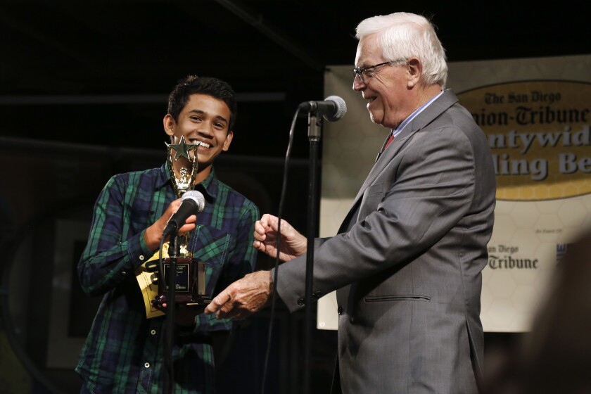 Yash Hande is presented a trophy by Rick Shea, right, President of the San Diego County Board of Education after winning the 48th annual San Diego Union-Tribune Countywide Spelling Bee.