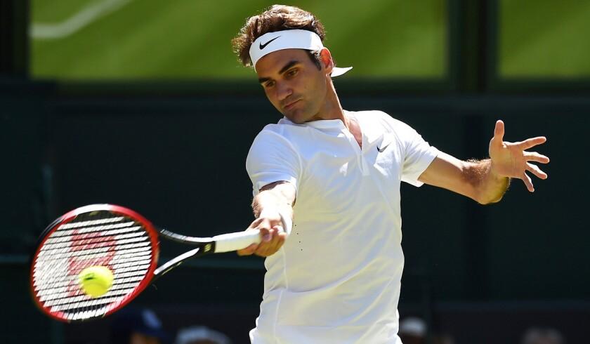 Roger Federer returns a serve to Damir Zumhur during a first round match at Wimbledon on Tuesday.