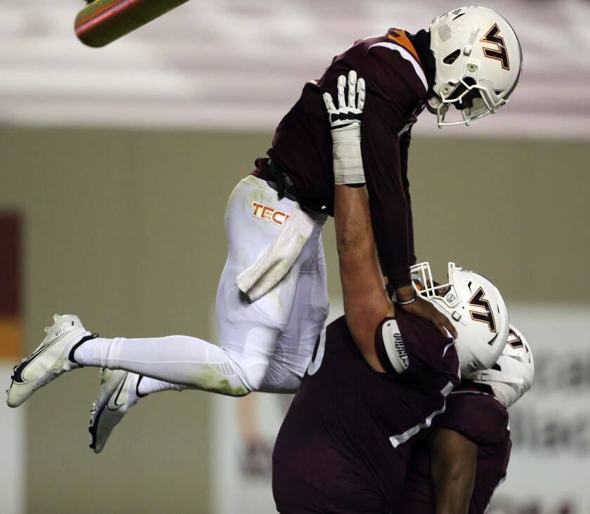 Virginia Tech quarterback Hendon Hooker, top, celebrates a touchdown with Christian Darrisaw in the fourth quarter of an NCAA college football game against Boston College in Blacksburg, Va., Saturday, Oct. 17, 2020. (Matt Gentry/The Roanoke Times via AP, Pool)