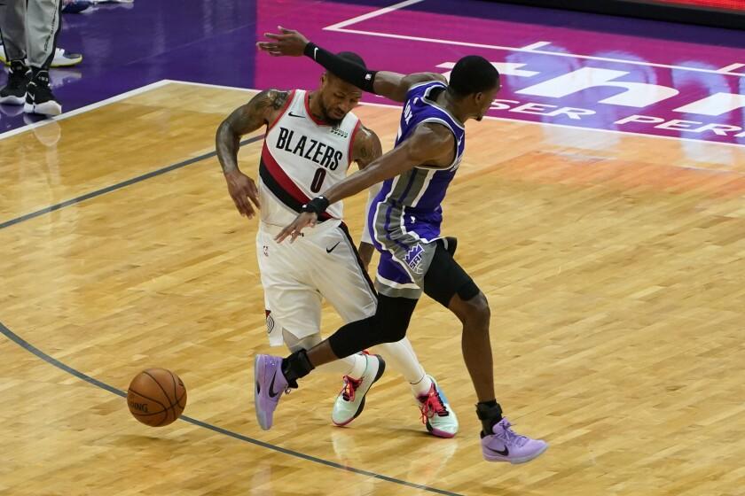 El jugador de los Trail Blazers de Portland Damian Lillard (izquierda) esquiva a De'Aaron Fox, de los Kings de Sacramento, en el segundo cuarto del juego de la NBA que enfrentó a ambos equipos, en Sacramento, California, el 13 de enero de 2021. (AP Foto/Rich Pedroncelli)