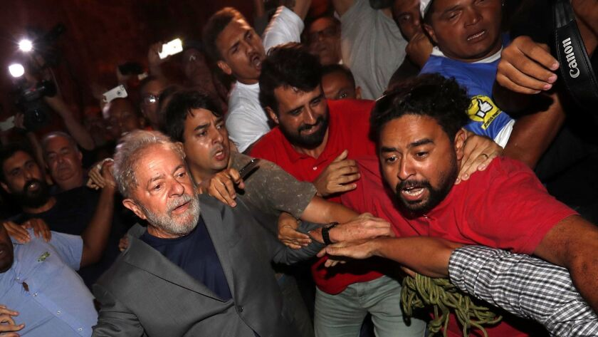Former Brazilian President Luiz Inacio Lula da Silva, in gray jacket, leaves the Steelworkers Union building in Sao Bernardo do Campo, Brazil, on April 7 2018, to turn himself in to the authorities.