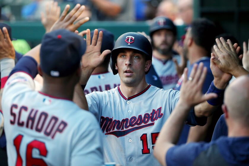 Minnesota Twins catcher Jason Castro celebrates with teammates after scoring a run against the Texas Rangers in August.
