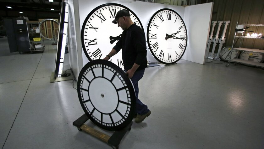 Dan LaMoore wheels a clock away from the test area as it is prepared to be shipped to a Tennessee school at the Electric Time Company in Medfield, Mass., Thursday, March 10, 2016. Most Americans will lose an hour of sleep this weekend, but gain an hour of evening light for months ahead, as Daylight