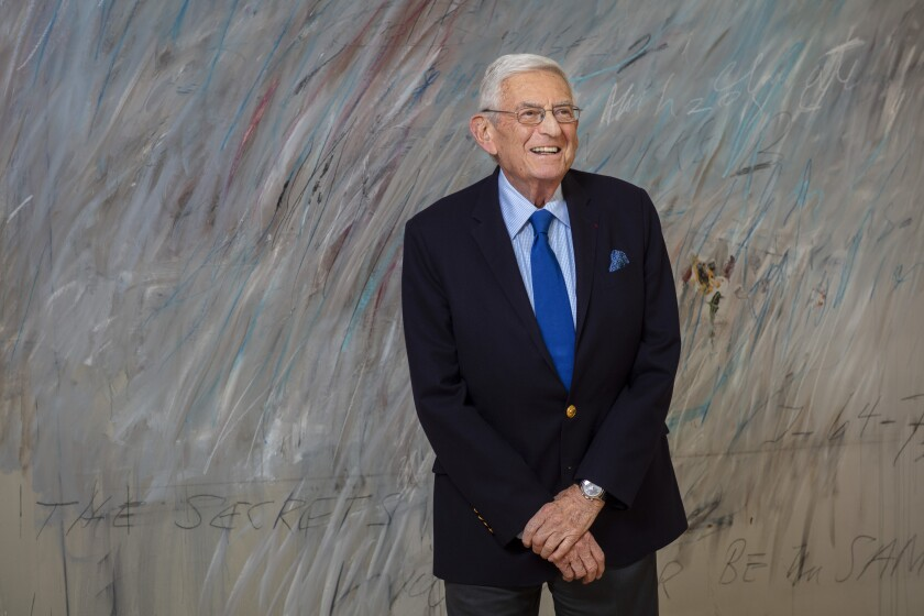 Eli Broad smiles and stands with his arms crossed in front of a large, gray-colored abstract painting