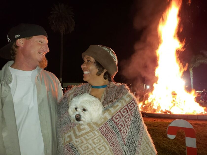 A couple and their dog bask in the glow of the Lemon Grove Bonfire in 2018.