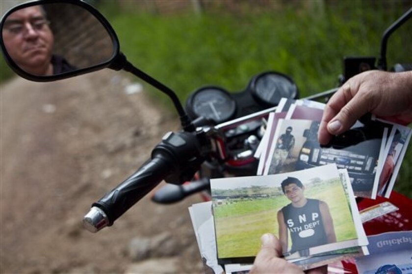 In this Oct 17, 2012 photo, Wilfredo Yanez, reflected on a mirror of his motorcycle, shows pictures of his late son Jaasiel Yanez, 15, at the site where he was shot dead allegedly by soldiers in Tegucigalpa, Honduras. According to his relatives, Jaasiel was killed by soldiers early Sunday, May 27,
