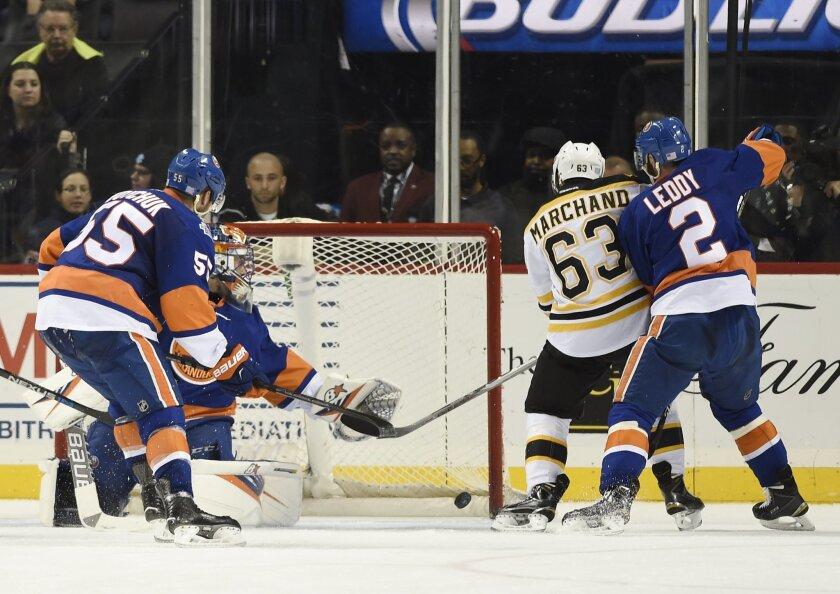 Boston Bruins' Brad Marchand (63) shoots the puck past New York Islanders goalie Jaroslav Halak (41) as Islanders Johnny Boychuk (55) and Nick Leddy (2) try to defend during the second period of an NHL hockey game on Sunday, Nov. 8, 2015, in New York. (AP Photo/Kathy Kmonicek)