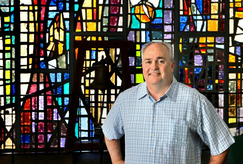 Portrait of Pastor Alvin Helms, of Carlsbad Community Church with stained glass in the church's Sanctuary that was completed in 1967. The church's adjacent Worship Center was completed in 1991 and seats 1,450 people.