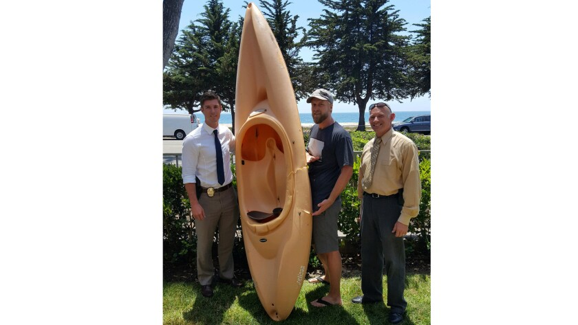 In a photo provided by Bret Z. Jackson, he stands with his kayak and two Santa Barbara officials aft