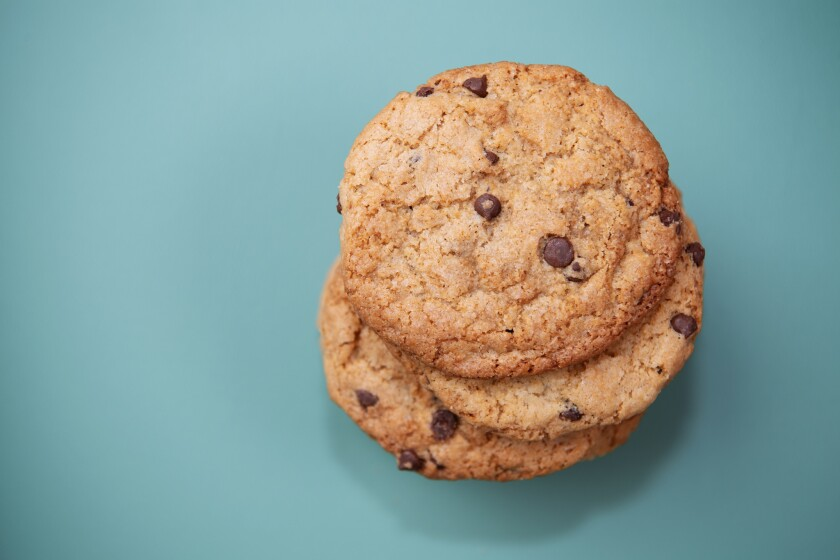 A stack of three chocolate chip cookies.