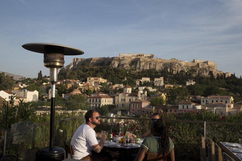 In this Tuesday, May 31, 2016 photo, tourists eat at a restaurant- cafe bar in front of the ancient Acropolis hill in central Athens. Greeks have woken up to a new wave of price hikes that have been demanded in return for more international bailout loans, with the highest increases targeting the ma