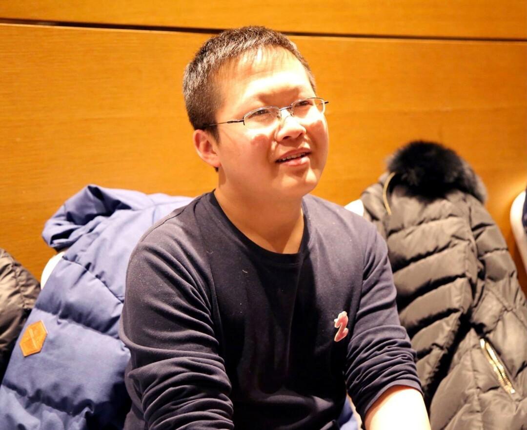 A man in glasses sits amid puffer coats