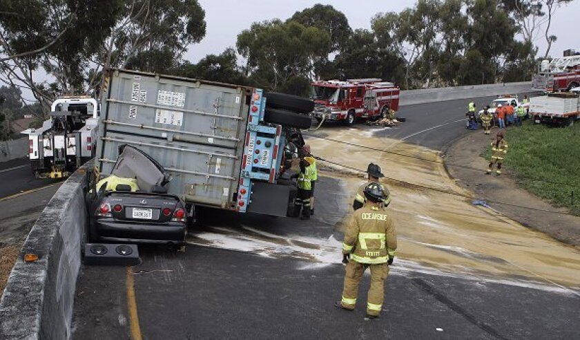 Emergency personnel respond at the scene of a fatality on an Interstate 5  ramp on Thursday morning in Oceanside. A semi truck tipped over crushing a car and killing the occupant of the car. A traffic alert was called, backing up traffic on southbound I-5.