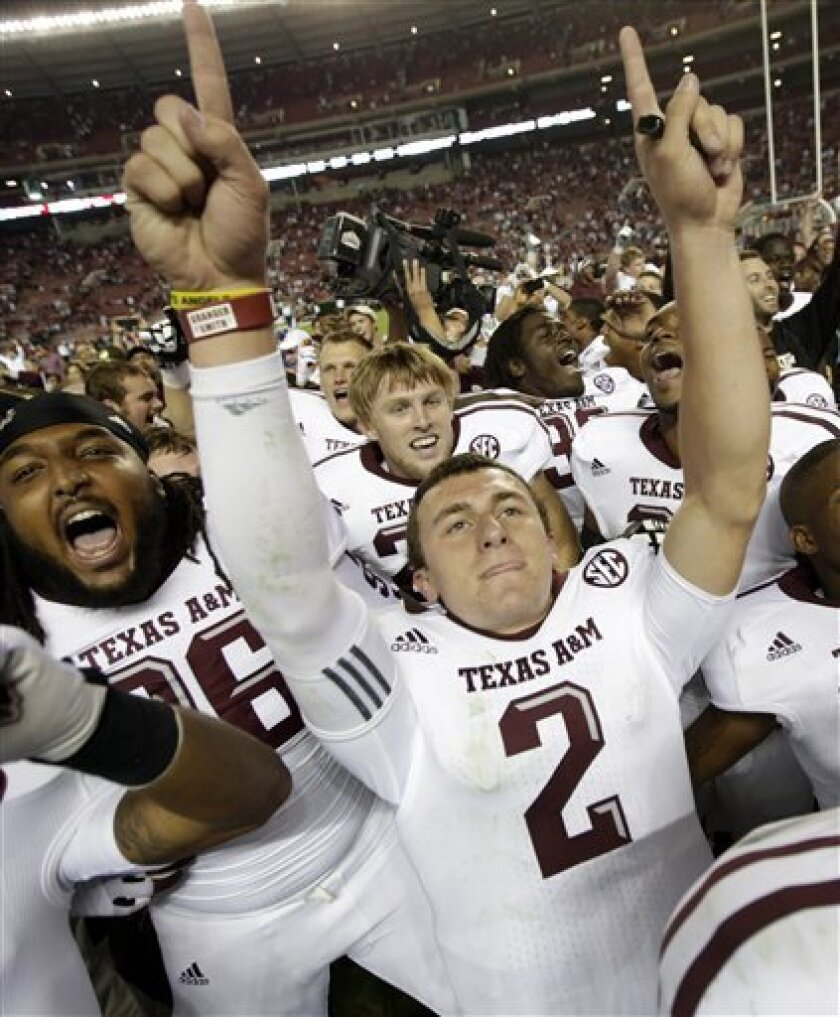 FILE - In this Nov. 10, 2012, file photo, Texas A&M quarterback Johnny Manziel (2) celebrates after the Aggies defeated top-ranked Alabama 29-24 in an NCAA college football game at Bryant-Denny Stadium in Tuscaloosa, Ala. Manziel could become the first freshman to win the Heisman Trophy when the award is presented on Saturday night. (AP Photo/Dave Martin, File)