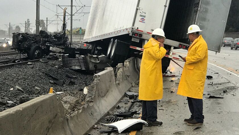 After hitting and crossing the center divider on the westbound 210 freeway, a truck caught fire and came to rest on the Gold Line Metro tracks.