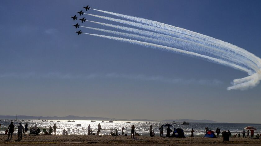 U.S. Air Force Thunderbirds take part in an airshow in the skies over Huntington Beach. The city is being sued by the state — and countersuing — over housing laws.