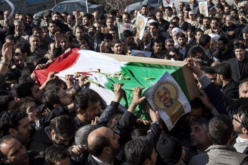 Iranian mourners carry the flag draped coffin of Gen. Hassan Shateri, shown in the poster, in Tehran, Iran, Thursday, Feb. 14, 2013. Prominent Iranian politicians and clerics led mourners at a funeral Thursday for a senior commander of the country's powerful Revolutionary Guards who was killed this