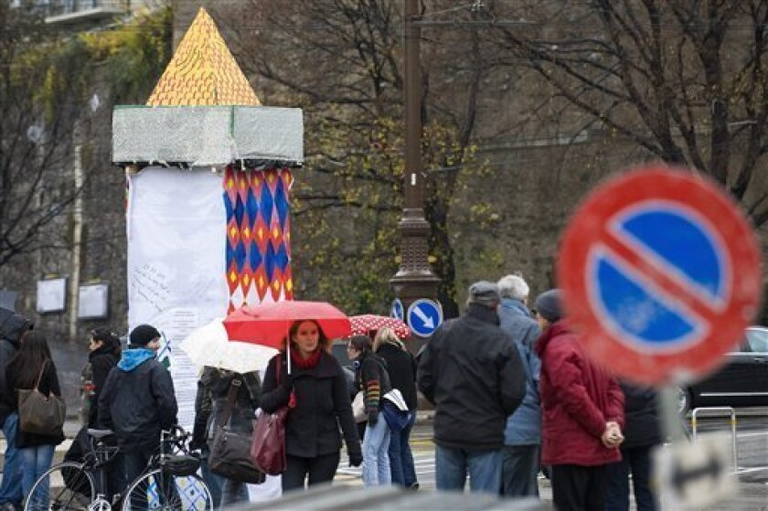 Protestors erect a symbolic minaret to protest against the results of a vote in Switzerland at the Place Neuve square in Geneva, Switzerland, Monday, Nov. 30, 2009. Swiss voters have approved a right-wing-backed proposal to ban construction of new minarets, initial projections showed on Sunday, a s