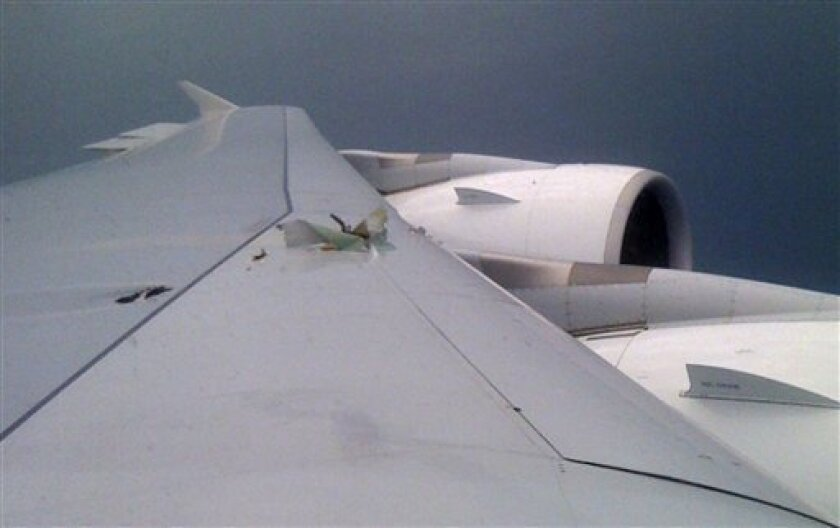 A damaged part of the left wing of a Qantas Airbus A380 is seen through a window of the passenger plane which made an emergency landing in Singapore's Changi International Airport after having engine problems Thursday, Nov. 4, 2010. Qantas grounded its Airbus A380 fleet after one of the superjumbo jets blew out an engine, shooting flames and raining large metal chunks before making a safe emergency landing in Singapore with 459 people aboard. (AP Photo/Matthew Hewitt)
