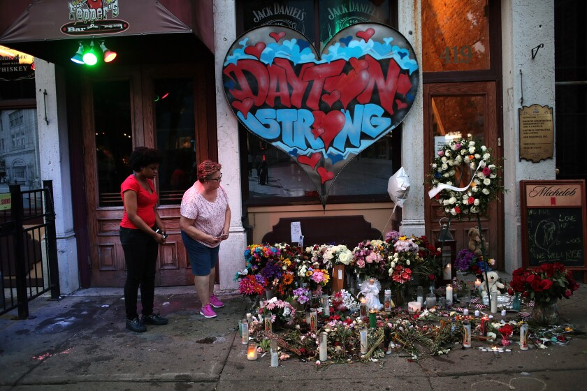 People look over a memorial to the nine people killed and 27 injured in the Aug. 4 mass shooting East 5th Street in Dayton, Ohio.