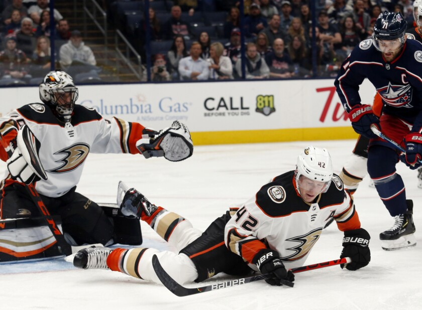 Ducks defenseman Josh Manson, center, tries to control the puck in front of goalie Ryan Miller and Blue Jackets forward Nick Foligno on Friday night.