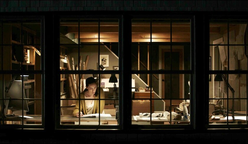 """A woman seen through a window reading a book in the movie """"The Night House."""""""