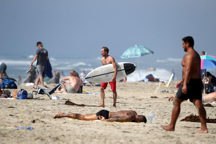 People enjoy a day at the beach on a warm day near the Huntington Beach Pier on Friday.