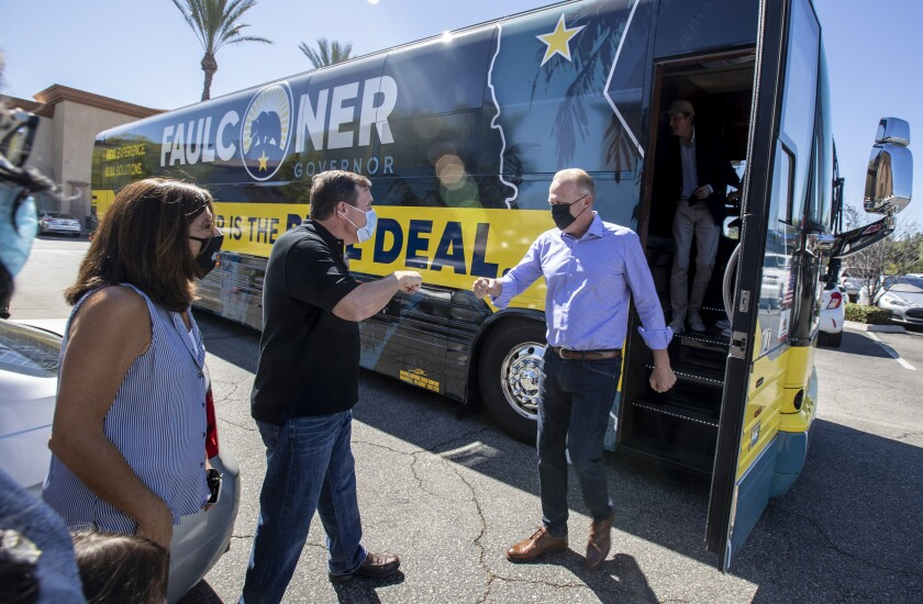 Kevin Faulconer, right, greets state Sen.  Scott Wilk, center, as he steps off his campaign bus