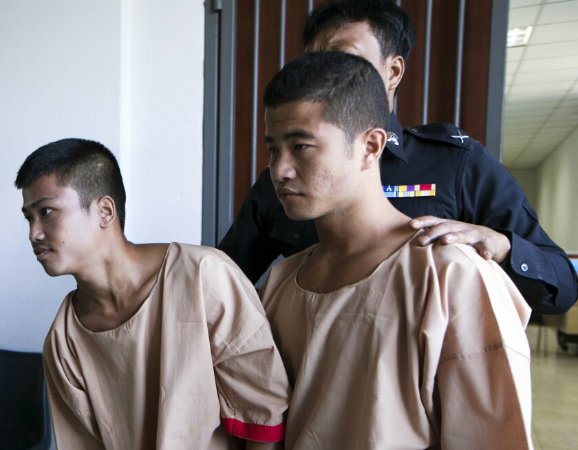 FILE - In this Dec. 24, 2015 file photo, Myanmar migrants Win Zaw Htun, right, and Zaw Lin, left, both 22, are escorted by officials after their guilty verdict at court in Koh Samui, Thailand. The two were convicted of killing 24-year-old British David Miller and raping and killing 23-year-old British Hannah Witheridge, whose battered bodies were found on a beach in 2014 on the island of Koh Tao in the Gulf of Thailand, a popular destination for diving. They had their death sentences commuted to life imprisonment Friday, Aug. 14, 2020 under a general clemency decree issued by King Maha Vajiralongkorn. (AP Photo/Wason Wanichakorn, File)