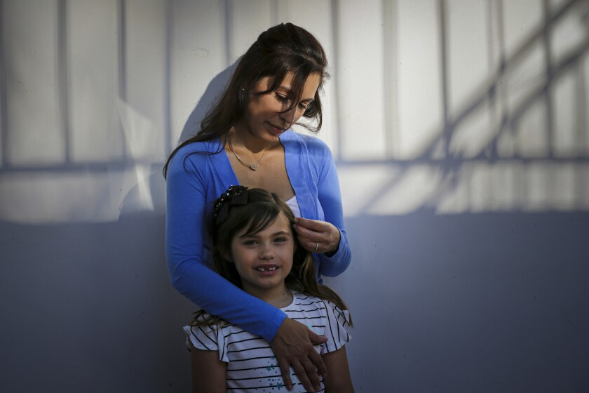 Alysia Padilla-Vaccaro stands with her 8-year-old daughter, Evangelina Vaccaro, who was born with no immune system.