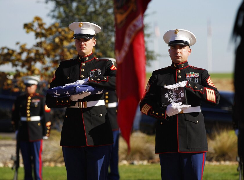 A Marine carries the ashes of Jeremy Sears, who killed himself, during a memorial for the veteran in October 2014 at Miramar National Cemetery. / photo by K.C. Alfred * U-T