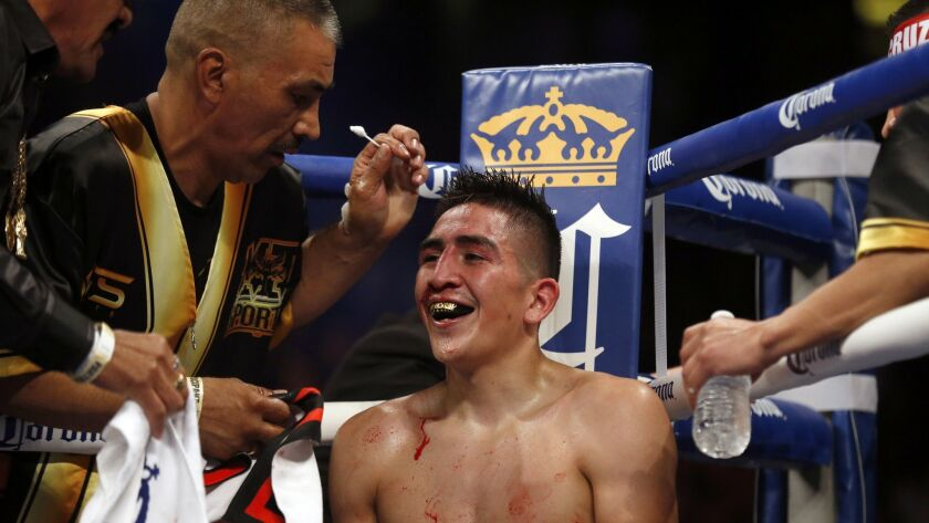 A bloodied but smiling Leo Santa Cruz sits in his corner between rounds before eventually beating Kiko Martinez by TKO during their World Featherweight Championship bout at the Honda Centerin Anaheim.