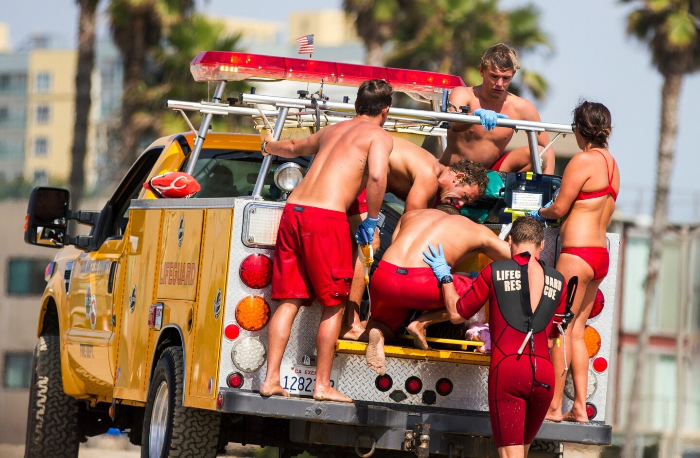 Lifeguards assist a person who was in the water and apparently struck by lightning at Venice Beach on Sunday.