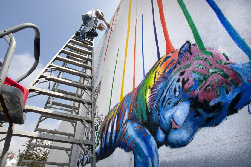 """Artist Michael Summers paints a mural called """"Catnap"""" in downtown Carlsbad on Tuesday. He is one of four artists commissioned to create murals in the Village."""