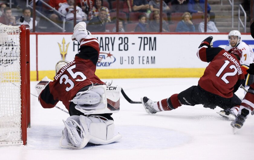 Arizona Coyotes' Louis Domingue (35) makes a diving save on a shot by Calgary Flames' T.J. Brodie (7) as Coyotes' Brad Richardson (12) also defends during the first period of an NHL hockey game Friday, Feb. 12, 2016, in Glendale, Ariz. (AP Photo/Ross D. Franklin)