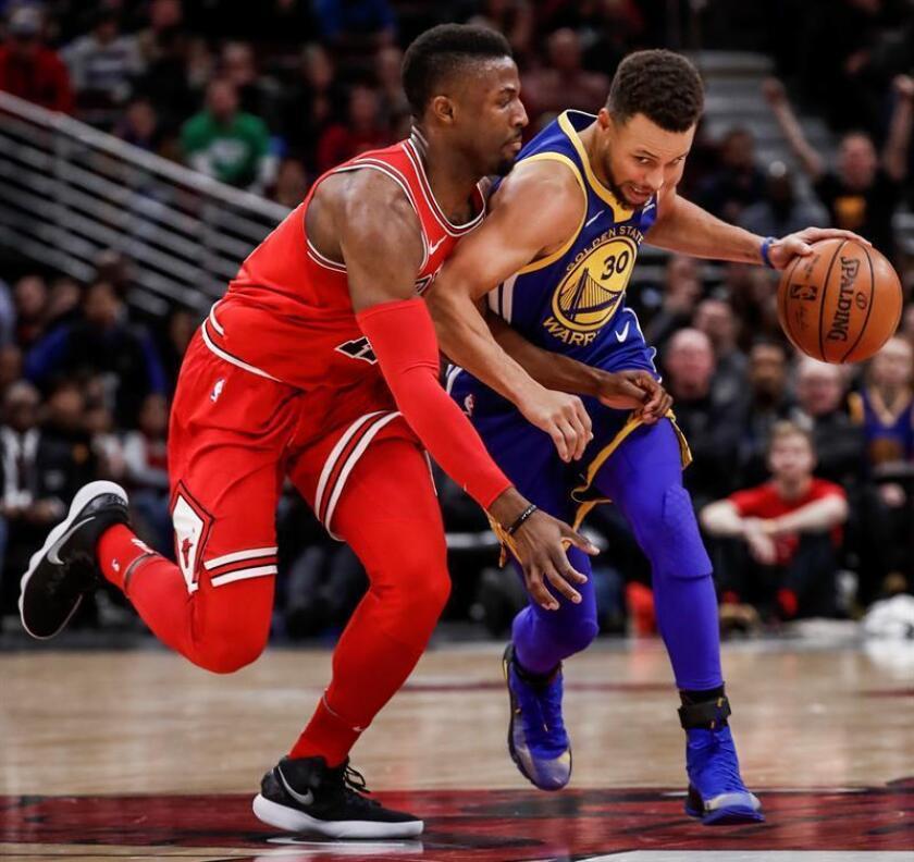 Stephen Curry (d) de Golden State Warriors disputa el balón con David Nwaba (i) de Bulls, durante un juego de la NBA entre Golden State Warriors y Chicago Bulls, jugado en United Center en Chicago (EE.UU.). EFE