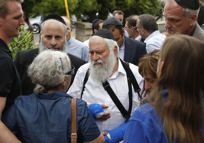 Rabbi Yisroel Goldstein, center, meets with members of the congregation of Chabad of Poway the day after a deadly shooting.