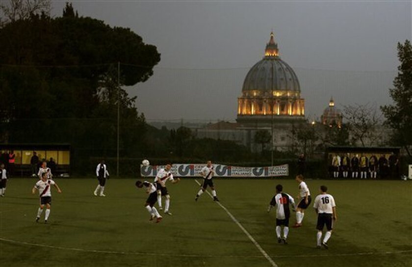 Players of Collegio San Paolo and North American Martyrs teams play their Clericus Cup soccer match, in Rome, Sunday, March 10, 2013. Vatican-supported soccer league matches went ahead as scheduled Sunday on a hill overlooking St. Peter's Basilica, shown in background. For the teams of seminaries,