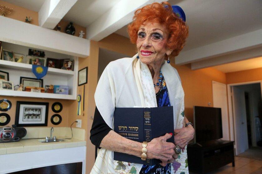 Lillian Wasserman of La Costa wears her prayer shawl and yarmulke while holding a book of Jewish prayers.