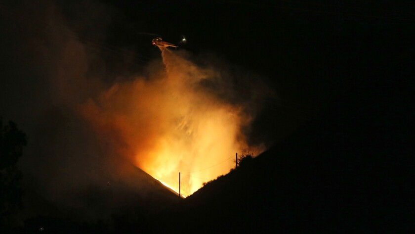 A firefighting helicopter makes a water drop on a wildfire in the hills of Porter Ranch on Oct 18.