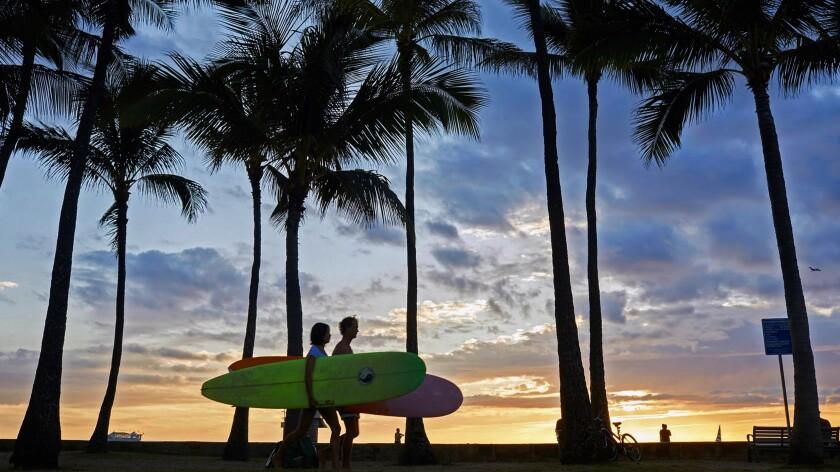 Surfers walk on a sidewalk along Waikiki Beach prior to the pandemic.