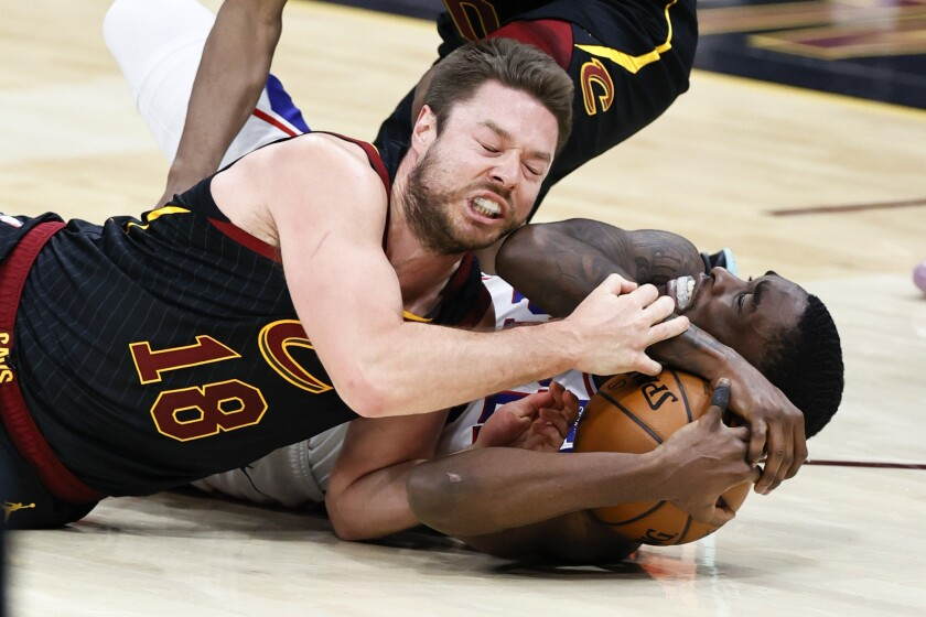 Cleveland Cavaliers' Matt Dellavedova, left, ties up Philadelphia 76ers' Shake Milton for a jump ball during the second half of an NBA basketball game Thursday, April 1, 2021, in Cleveland. (AP Photo/Ron Schwane)
