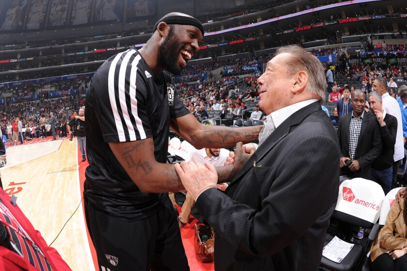 Not quite how he's seen today: Clippers owner Donald Sterling, right, with Reggie Evans of the Brooklyn Nets during a game last year.